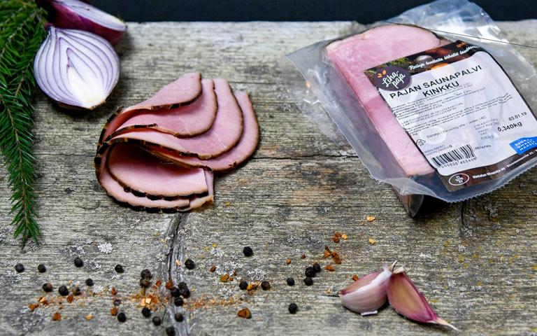 Yläneläisen Lihapajan tuotepakkaus ja leikkeleitä leikkuulaudalla.